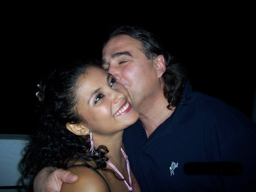 A smiling Latina is being kissed on the cheek by her foreign lover
